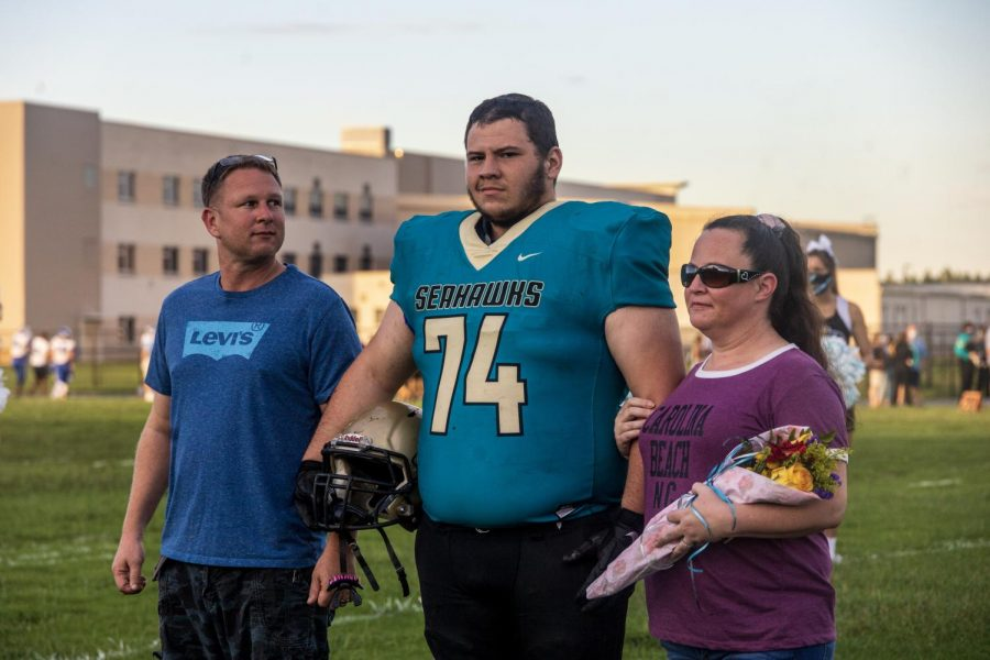 Walking across the field one final time on his senior night with  his mom (Kayla Clark) and his dad (Byron Clark).